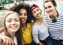 Multinational girl friends in the park selfie stock images