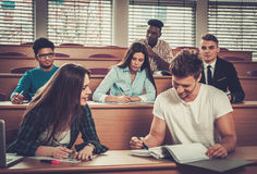 Multinational group of cheerful students taking an active part in a lesson while sitting in a lecture Hall. Stock Photo