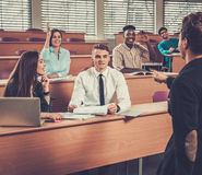 Multinational group of cheerful students taking an active part in a lesson while sitting in a lecture Hall. Royalty Free Stock Photos