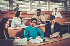 Multinational group of cheerful students taking an active part in a lesson while sitting in a lecture Hall. stock image