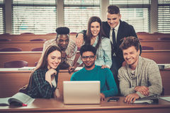 Multinational group of cheerful students taking an active part in a lesson while sitting in a lecture Hall. Royalty Free Stock Image