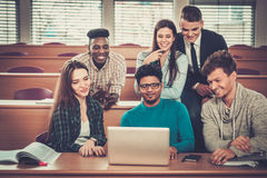 Multinational group of cheerful students taking an active part in a lesson while sitting in a lecture Hall. Stock Photography