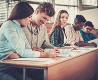 Multinational group of cheerful students taking an active part in a lesson while sitting in a lecture Hall. Stock Images