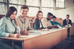 Multinational group of cheerful students taking an active part in a lesson while sitting in a lecture Hall. royalty free stock photography