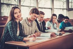 Multinational group of cheerful students taking an active part in a lesson while sitting in a lecture  hall. Multinational group of cheerful students taking an Stock Photos