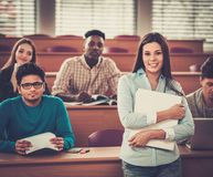 Multinational group of cheerful students taking an active part in a lesson while sitting in a lecture  hall. Stock Photos