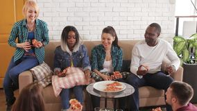 Multinational group eats pizza indoor and talk at home stock video footage