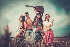 Multinational hippie friends with guitar in a wheat field.  Royalty Free Stock Images