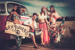 Multinational hippie hitchhikers with guitar and luggage on a road.  Royalty Free Stock Images