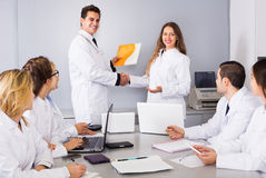 Multinational interns and professor cooperating Royalty Free Stock Images