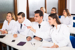 Multinational interns and professor having discussion Stock Photos