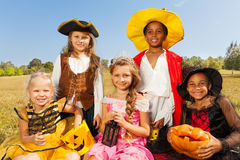 Multinational kids in Halloween costumes. Sitting together on the grass with pumpkin and look happily stock image
