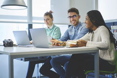 Multinational team of business school students sitting in workplace with good mood royalty free stock images
