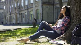 Multinational young woman sitting calmly under tree with closed eyes, relaxation. Stock footage stock video