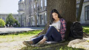Multinational young woman taking notes in notebook sitting under tree, essay Stock Images