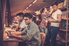 Multinationale groep vrolijke studenten die in de universitaire bibliotheek bestuderen Royalty-vrije Stock Afbeelding