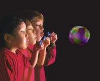 Multinationale Kinder, die Luftblase durchbrennen lizenzfreie stockfotografie
