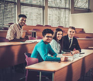 Multinationell grupp av gladlynta studenter som tar en aktiv del i en kurs, medan sitta i en hörsal royaltyfri foto