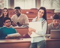 Multinationell grupp av gladlynta studenter som tar en aktiv del i en kurs, medan sitta i en hörsal arkivbilder