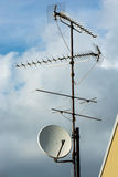 Multiple Aerials on Rooftop. In Front of Cloudy Sky Royalty Free Stock Image