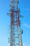 Multiple antennas of transmitting tower against blue sky. An art of telecommunication engineering Royalty Free Stock Image