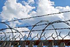 Multiple Barriers. Wooden fence, chain-link fence, barbed wire and razor wire as protective barriers Royalty Free Stock Photography