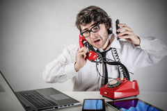 Multiple calls. Businessman answering multiple calls at the same time royalty free stock photos
