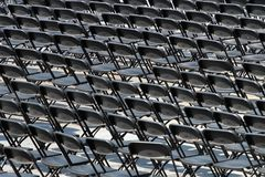 Multiple chairs outdoor, many black chair backs.  stock photography
