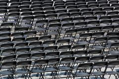 Multiple chairs outdoor, many black chair backs stock image
