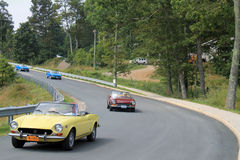 Multiple classic italian sports cars on road Stock Image