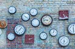Multiple clock. Plurality of the different clocks on the old brick wall Royalty Free Stock Photos