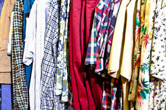 Multiple coat hanger. Sweaters and t-shirts on rack for sale in second hand store Royalty Free Stock Images