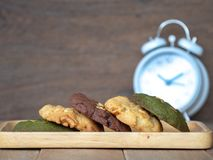 Multiple color cookies inclusive peanut butter, green tea cookies, and Chocolate Chip Cookies. Overlaid by alternating colors on w. Ood plate. White clock placed stock photography