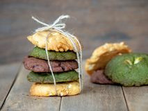 Multiple color cookies inclusive peanut butter, green tea cookies, and Chocolate Chip Cookies. Overlaid by alternating colors on w. Ood table stock images