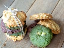 Multiple color cookies inclusive peanut butter, green tea cookies, and Chocolate Chip Cookies. Overlaid by alternating colors on w. Ood table royalty free stock photo