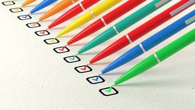 Multiple colored ball pens crossing off items from a checklist Royalty Free Stock Photography