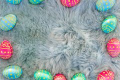 Chocolate Easter eggs on fur, pink, blue and green eggs, easter backgroung stock image