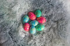 Chocolate Easter eggs on fur, pink, blue and green eggs, easter backgroung royalty free stock photos