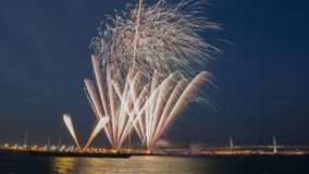 Multiple colorful fireworks burst in the blue sky with distant city lights and sea waater Stock Images