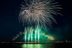 Multiple colorful fireworks burst in the night sky with light trails over the sea Royalty Free Stock Images