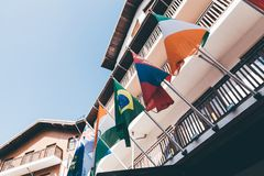 National flags fixed to facade of house. Multiple colorful national flags of different countries fixed to wooden facade of houses on sunny summer day with clear Royalty Free Stock Photos