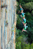 Multiple continues Shoot of falling Rock Climber. Female Climber falling down off high vertical rocky Wall combined from multiple high speed shoot Royalty Free Stock Photo