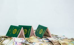 Multiple Ecowas Nigeria International Passport on a heap of local naira currencies royalty free stock image