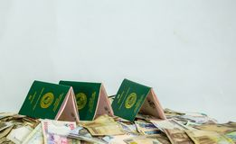 Multiple Ecowas Nigeria International Passport on a heap of local naira currencies stock photography