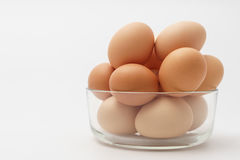 Multiple eggs in a glass bowl. On a white background Stock Images