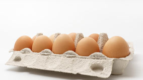 Multiple eggs in a paper package. On a white background Stock Photos