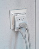Multiple electrical plugs in wall outlet Stock Photography