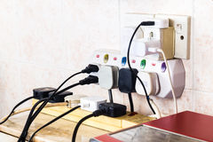 Multiple electricity plugs on adapter risk overloading and dange Stock Photography