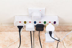 Multiple electricity plugs attached to multi adapter is dangerou Stock Photos