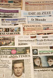 Multiple European newspapers in a pile. Front pages vertical Royalty Free Stock Photo